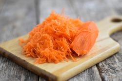 Grated carrot on a wooden background