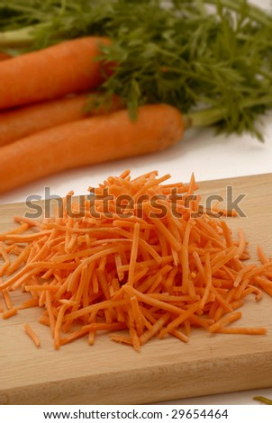 Grated carrots in a wood table and carrot background.