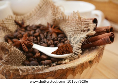 grated coffee in white porcelain spoon on blurred  roasted coffee beans background. aroma coffee ingredients. selective focus. #1013076286