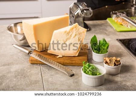 grated parmesan cheese and metal grater on wooden board with greenery