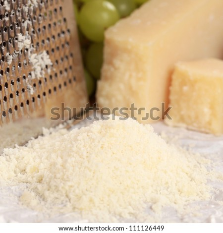 Grated Parmesan cheese with grapes in the background. Selective focus.