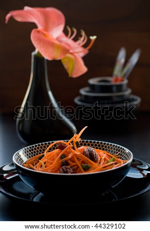 Grated raw carrots with raisins and nuts in a bowl
