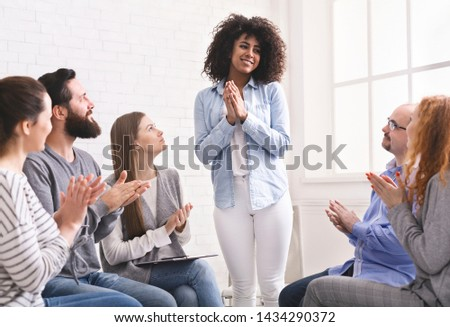 Grateful african woman sharing her progress with rehab group at therapy session, empty space