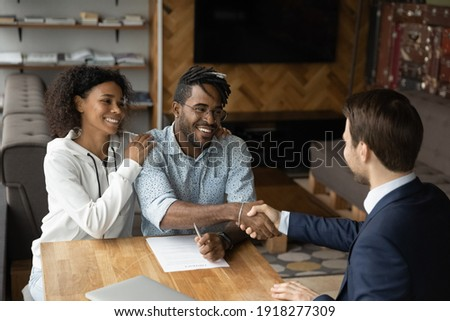 Grateful black family couple handshake with bank manager insurer lawyer thank for consultation before sign contract. Satisfied young african husband wife real estate buyers make deal with male broker