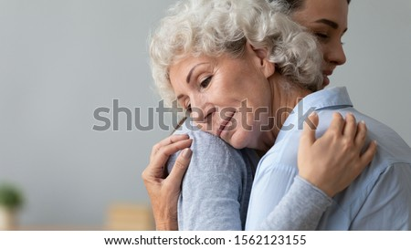 Grateful calm senior grandma mother embrace young adult daughter hug grandchild, two age generations women bonding give support and comfort, helping sharing love care with older grandparent concept