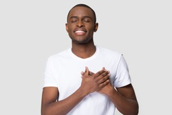 Grateful happy pleased african man holding hands on chest to heart feeling love appreciation gratitude honesty, thankful sincere proud black guy thanking isolated on white studio blank background