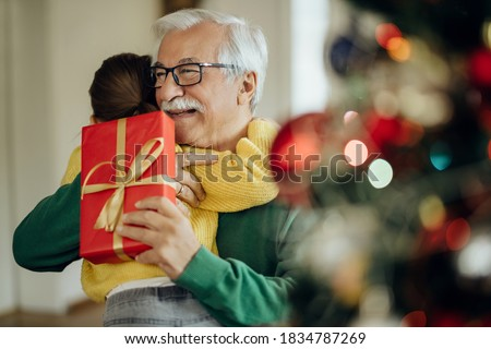 Grateful little girl embracing her grandfather while receiving Christmas present at home. Focus is on man.  Foto stock ©