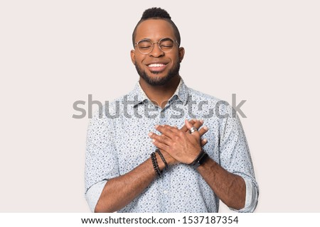Grateful smiling african American man in glasses isolated on grey studio background hold hands on heart chest feel peace, happy thankful biracial male thanking god believe in good luck, faith concept
