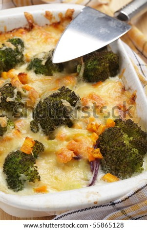 Gratin with broccoli, carrot, onion and cheese in white casserole