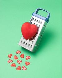 Grating big red heart and making a lot of small ones. Valentines day concept.