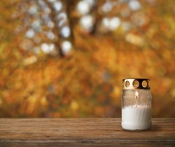 Grave candle on autumn background, All Saint's Day
