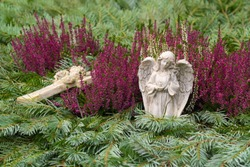 Grave decoration with an angel and a cross, fir branches and winter flowering heather