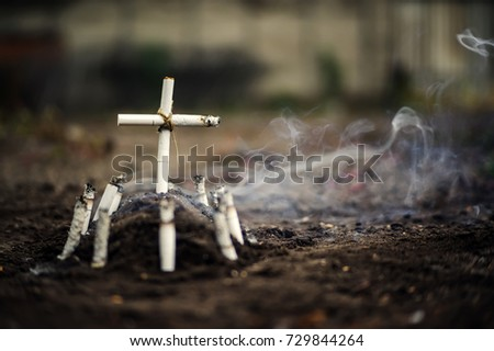 Grave of bad habit. Anti tobacco a conceptual photo with copyspace. Tomb with a cross made of cigarettes and cigarette butts on the ground.