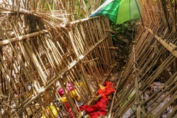 Grave of bamboo sticks in cemetery in Terunyan village. Traditional Kuburan in Bali, Indonesia. Bodies are buried above ground. Human skull among colored fabrics. Part of a combined pagan Hindu belief