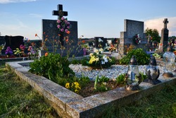 Grave / tombstone in the cemetery / graveyard. All Saints Day / All Hallows / 1st November. Flowers and candles on tomb stone in churchyard. Slovakia, Europe