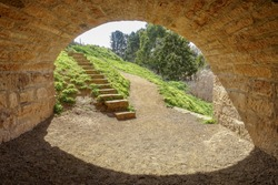 Gravel footpath going under an historical old stone bridge hole/tunnel with stairs leading up to the bridge. Richmond Bridge, TAS Australia.