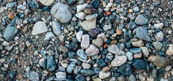 Gravel pattern of colored stones on the river coast. Texture of various pebbles, abstract background, top view.
