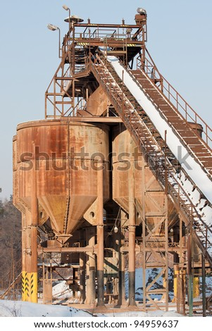 Gravel pit, Belt conveyors and silos in winter - stock photo