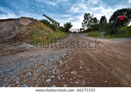 Gravel pit with crane in background