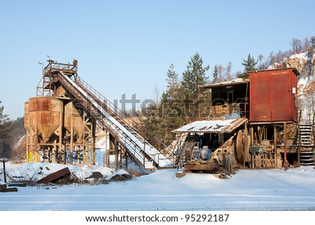 Gravel quarry, belt conveyors and silos in winter