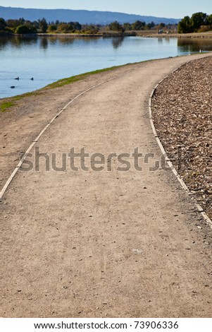 GRavel road in a park winding right from the lake shore.