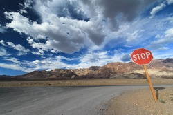 Gravel Road in Death Valley national park with Stop Sign, blue sky with cloud. Nevada State, USA.