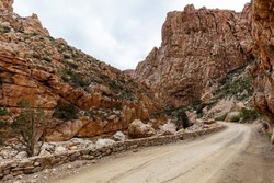 Gravel road of Swartberg pass winding through contorted rock formations