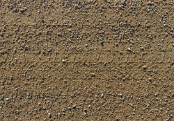 Gravel road surface with trail of wheel.