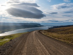Gravel road with dramatic cloudy sky in southern fjords, Iceland