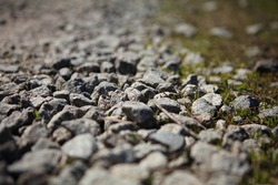 Gravel texture. pebble stones texture. Bottom view of a dirt gravel road. Pebble stone background. Light grey closeup small rocks. Focused in front. Rocks on the Road.