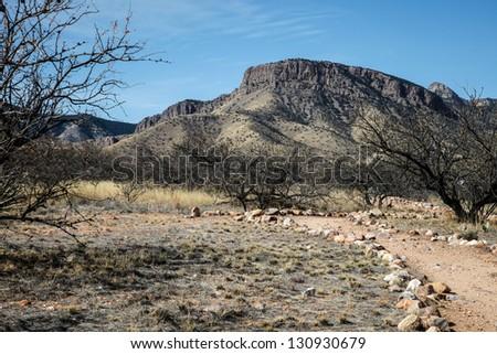 Gravel trail curves below semi-desert mountain area/Semi-Desert Trail Leads Towards Flat Top Mountain in Rural Arid Terrain/Dry rocky pathway in arid countryside
