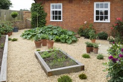 Gravel vegetable garden or back yard with wooden raised beds made from oak sleepers