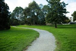 Gravel Walking track through grassy park in Glen Iris, Victoria Australia. Part of Ferndale Trail Ashburton. Textured green grass and trees and grainy gravel.