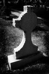 Gravestone cross in cemetery representing death marker grave stone