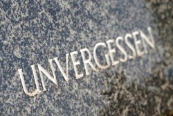 Gravestone in a cemetery with the word unforgotten