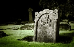 Gravestone with skull and bones in old cemetery, dramatic light