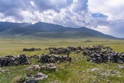 Gravestones and graveyard in the steppe of Mongolia with mountains and hills near Bayan Lake.
