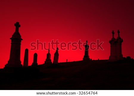 Gravestones silhouetted against a foreboding red sky.
