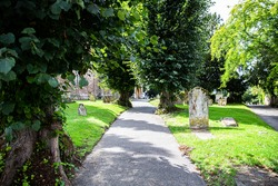 graveyard / cemetery path in the sunshine with leafy green trees in the summer