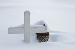 Graveyard in winter, a small wooden cross and a lantern covered in snow