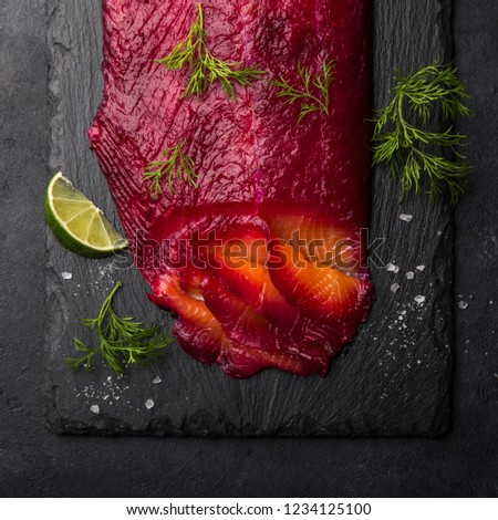 Gravlax,  scandinavian beet cured salmon on black slate board, top view, square image