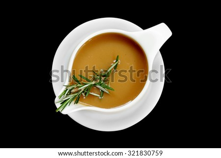 Gravy sauce with rosemary in a gravy boat on black background, isolated Сток-фото ©
