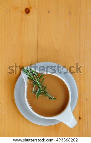 Gravy sauce with rosemary in a gravy boat on wooden table. Top view. Сток-фото ©