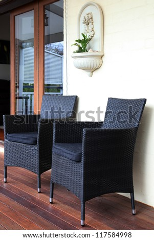 gray and black rattan tub chairs on deck