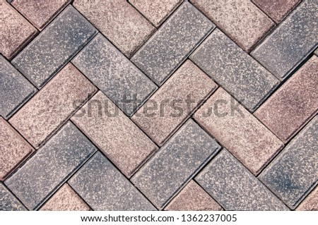 Gray and dark gray paving slabs, after the rain. Geometric ornament. The texture and background of the stone.
