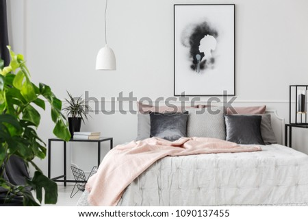 Gray and silver cushions lying on a bed with white sheets and pink blanket in feminine bedroom interior