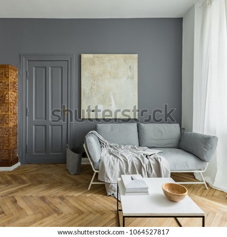Gray and white living room with couch, coffee table and vintage tiled stove #1064527817
