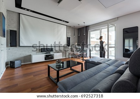 Gray and white living room with sofa, table, balcony and projector screen #692527318
