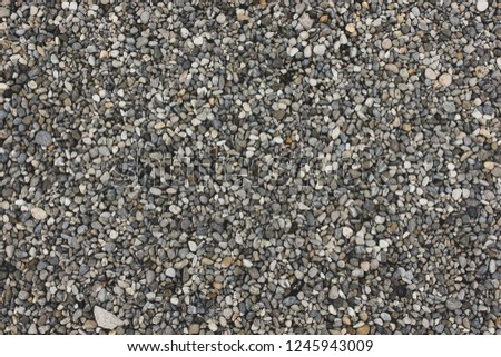 Gray and white natural sand and stones texture of ground. Dotted grey rock floor with place for text #1245943009