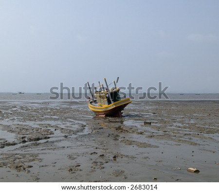 Gray and yellow fishing boat stranded in the mud. Chonburi province, Thailand